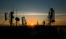 Antenas das comunicações de encontro ao céu azul Fotografia de Stock