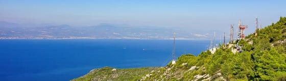 Antenas de la telecomunicación al borde de una montaña cerca del mar imagen de archivo