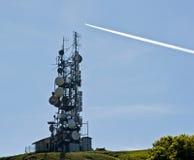 Antenas de la telecomunicación y rastro del jet Foto de archivo