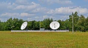 Antenas de satélite, árboles verdes y cielo azul de la tempestad de truenos, Fotografía de archivo