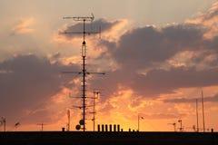 Antenas de televisão no telhado representado no por do sol fotos de stock