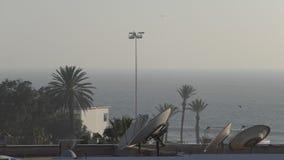 Antenas parabólicas, palmeras y mar antes de la tormenta almacen de metraje de vídeo