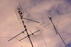 Antenas sobre un cielo rosado fotos de archivo