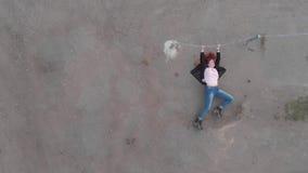 Antenn av det kedjade fast fångade kvinnabegreppet som agerar som bärande jeans för aktrisvisningflagga och den rosa t-skjortan m arkivfilmer
