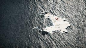 Antenn av det röda flygplanet som flyger över det smältande isberget Arkivfoton