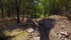 Antenn av grävde diken för rörledningar och kommunikationer på en konstruktionsplats Vattenrörledningrekonstruktion och arkivfilmer