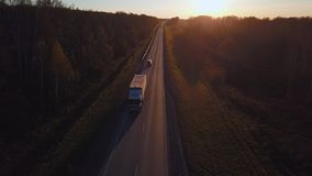 Antenn: bilen med behållaren rider på vägen till solnedgången Lastbilen rider huvudvägen arkivfilmer