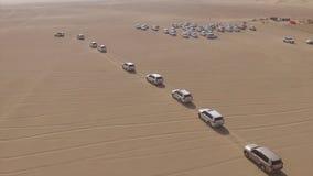 ANTENN: bilkörning till och med öken materiel Flyg- sikt av 4x4 av väglandmedlet som tar turister på ökendyn Arkivbild
