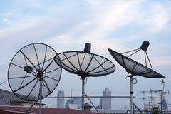 Antenn för satellit- disk på taköverkant bland staden Arkivbild