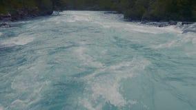Antenn - flyga lågt ovanför turkosfärgfloden som snider dess väg till och med Springet Valley arkivfilmer