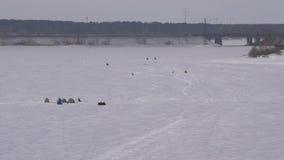 Antenn gruppfiskare på den djupfrysta sjön i vinter arkivfilmer