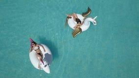 Antenn - härliga flickor i en bikini på en uppblåsbar pegasus och enhörningmadrass i pölen Den unga kvinnan tycker om a lager videofilmer
