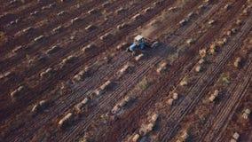 Antenn lodlinje - traktoren med fåran plöjer att ploga ett fält stock video