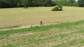 Antenn: man som cyklar längs landsvägen till och med kultiverade fält och jordbruksmark, solig dag, vänligt trans. för eco på cir lager videofilmer