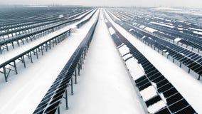 ANTENN: Photovoltaic i vintern som täckas med snö Solpaneler bland snödrivorna som täckas med snö _ arkivfilmer