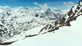 Antenn: skida turnera bergsbestigningsnöberget, panoramautsikt på fjällängarna som erövrar, flyga över fotvandrare på snöig bergö stock video