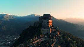 Antenn: surrflyget på den gamla medeltida abbotskloster sätta sig på bergöverkanten, snöig fjällängar för bakgrund på soluppgång  stock video