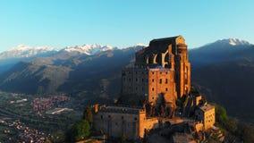 Antenn: surrflyget på den gamla medeltida abbotskloster sätta sig på bergöverkanten, snöig fjällängar för bakgrund på soluppgång  arkivfilmer