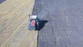 Antenn - traktoren med fåra fyra plöjer att ploga ett fält lager videofilmer