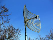 Antenna. Embosomed in trees on blue sky background Stock Photos