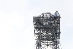 Antenna alta della torre di comunicazioni delle cellule del metallo contro un cielo leggero Fotografia Stock Libera da Diritti