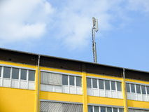 Antenna. Atop of a yellow building against a blue sky Stock Photography