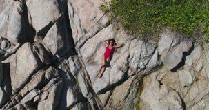 Antenna: Bella ragazza in bikini rosso che si trova e che posa sulle pietre video d archivio