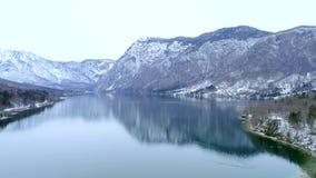 Antenna che sorvola il lago Bohinj vicino alle montagne video d archivio