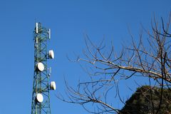 Antenna of Communication tower with blue sky and leafless trees. Antenna of Communication Building tower with blue sky and leafless trees Stock Photography