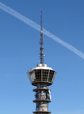 Antenna communications tower. Tower of antenna in blue sky, with a condensation strip from a plane Royalty Free Stock Photos