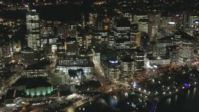 Antenna, costruzioni della città e vie illuminate alla notte, pentola stock footage