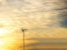 Antenna della TV sui precedenti del tramonto con il flusso continuo leggero delle nuvole gialle fotografia stock