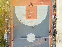 Antenna direttamente sopra la vista della concorrenza del campo da pallacanestro della via con il gioco della gente fotografia stock