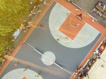 Antenna direttamente sopra la vista della concorrenza del campo da pallacanestro della via con il gioco della gente fotografie stock