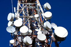 Antenna Drums on Mobile Phone Mast. Red mobile phone masts with white antennas against blue sky stock images