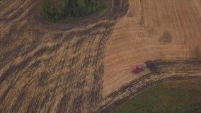 ANTENNA: fucilazione al fuco sopra il campo di terreno arabile Un trattore rosso rimuove il campo nella caduta video d archivio