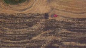 ANTENNA: fucilazione al fuco sopra il campo di terreno arabile Un trattore rosso rimuove il campo nella caduta archivi video