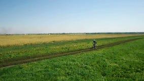 ANTENNA: Giovane che cicla sulla bicicletta alla strada rurale attraverso il campo verde e giallo archivi video