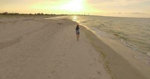 antenna 4k - la bella ragazza cammina lungo Sandy Beach al tramonto archivi video