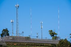 Antenna posts blue sky background. Telecom antenna posts in country side symbol for technology of communication developing Royalty Free Stock Image