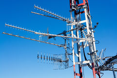 Antenna repeater messy mast in blue sky Stock Photo