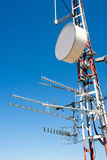 Antenna repeater messy mast in blue sky Royalty Free Stock Photos