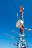 Antenna repeater messy mast in blue sky Royalty Free Stock Photography