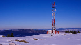 Antenna repeater tower on top of snowy mountain Royalty Free Stock Images