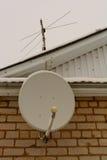 Antenna satellitare sul muro di mattoni e sul tetto della casa Fotografia Stock Libera da Diritti