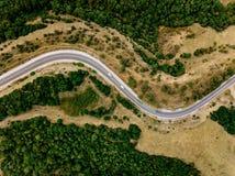 Antenna sopra la vista di un paesaggio rurale con una strada curvy che lo passa in Grecia fotografia stock libera da diritti