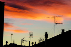Antennas and chimneys at sunset Stock Photography