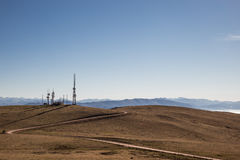 Antennas. A curvy road towards some antennas on a top of mountain, under a blue, empty sky royalty free stock photo