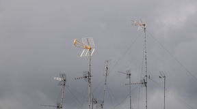 Antennas over the roofs against grey sky Stock Image