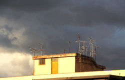 Antennas on a roof, against a cloudy sky Royalty Free Stock Images
